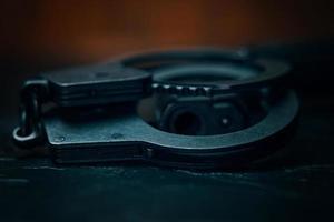 handboeien en de snuit van een close-up van een pistool foto
