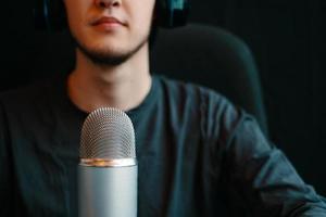 man zendt uit in de lucht op een luidspreker in podcast studio met microfoon