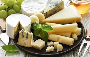verschillende soorten kaas op een witte houten achtergrond foto