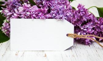 lila bloemen met een lege tag op een oude houten achtergrond foto