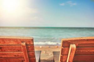 twee houten traliewerk ligbedden op het strand foto