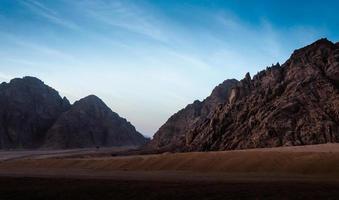 woestijn met rotsachtige bergen in de avond foto