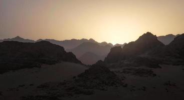 rotsachtige bergen met een ondergaande zon foto