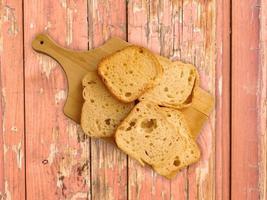 gesneden toast op een houten snijplank op een houten tafel achtergrond foto