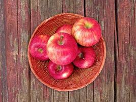 rode appels op een rieten plaat op een houten tafel achtergrond foto