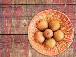 kiwi's op een rieten plaat op een houten tafel achtergrond foto