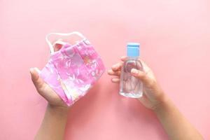 de handen van het kind met een roze masker en handdesinfecterend middel