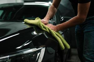 man reinigt de carrosserie met een handdoek foto