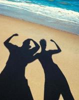 silhouetten van twee mensen op een strand