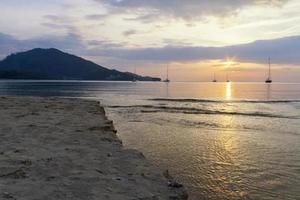 zonsondergang op het strand van phuket, thailand foto