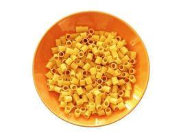 buis pasta in een oranje kom geïsoleerd op een witte achtergrond foto