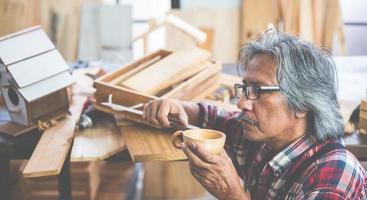 man die een houten beker maakt foto