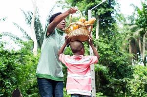 moeder zet de voedselmand op het hoofd van haar zoon zoals hij wil
