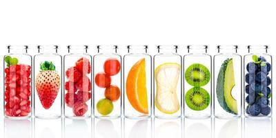 Zelfgemaakte huidverzorging met fruitingrediënten van avocado, sinaasappel, bosbes, granaatappel, aardbei en framboos in glazen flessen geïsoleerd op een witte achtergrond foto