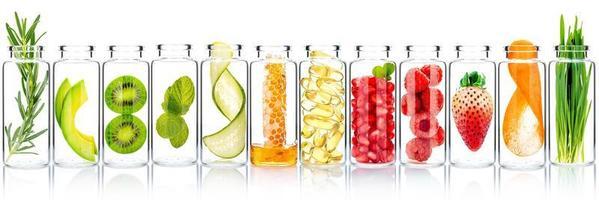 zelfgemaakte huidverzorging met fruitingrediënten van avocado, sinaasappel, bosbes, granaatappel, kiwi, citroen, komkommer, tamarinde, aardbei en framboos in glazen flessen geïsoleerd op een witte achtergrond. foto