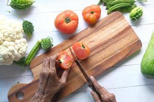 oudere vrouwen snijden tomaten op een snijplank van boven naar beneden