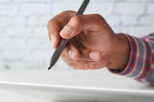 hand met stylus schrijven op digitale tablet