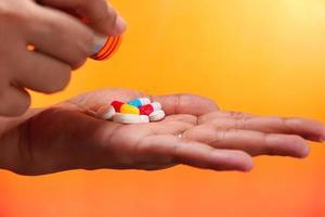 close-up van de handen van de vrouw met pillen op een oranje achtergrond foto
