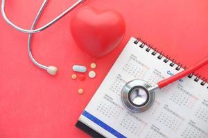 bovenaanzicht van pillen en stethoscoop op kalender