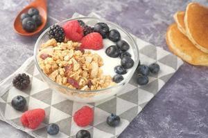 muesli met yoghurt en bessen in kom op neutrale achtergrond foto