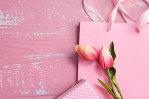 bovenaanzicht van roze kleur cadeauzakje en bloemen