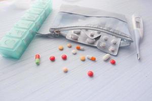 blisterverpakking, thermometer en pillen op witte achtergrond