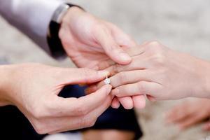 close-up handen van bruidegom en bruid trouwring dragen voor ceremonie foto
