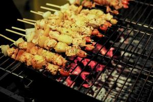 close-up rij van vlees bbq op de metalen grill met wazig hete houtskool foto