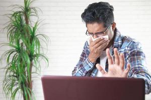 man hoesten en niest bezig met laptop foto