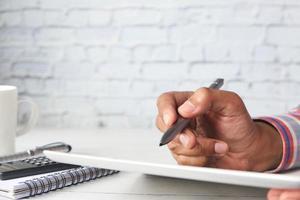 man's hand bezig met digitale tablet met stylus