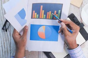 bovenaanzicht van de hand met pen analyseren staafdiagram op papier