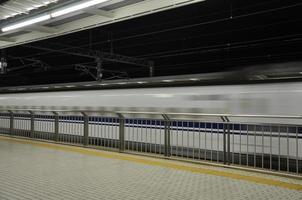 wazig filmbeeld van bewegende hogesnelheidstrein langs het station foto