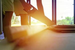 close-up van een persoon met behulp van een handzaag binnenshuis in aanbouw foto