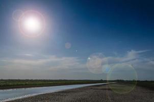 zon flair en strand foto