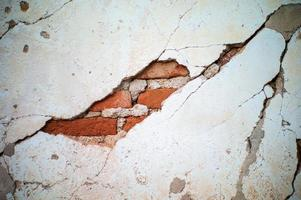 achtergrond en textuur van gebroken cementmuur met binnen metselaars foto