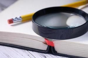 close-up van open boek en vergrootglas