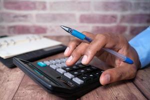 close-up van iemands hand met behulp van rekenmachine