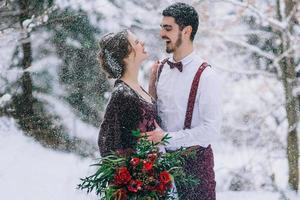 bruidegom in een bruin en bruid in bordeaux in de bergen foto
