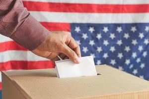 een stembiljet in het stemhokje steken foto