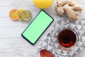 bovenaanzicht van gemberthee en slimme telefoon met groen scherm op houten achtergrond