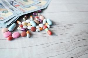 gezondheidszorg kosten concept met pillen en contant geld op tafel foto