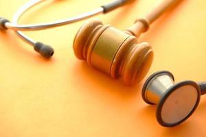 hamer en een stethoscoop op oranje achtergrond foto