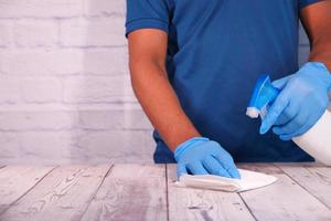 persoon die een desinfecterende spray gebruikt om het tafeloppervlak schoon te maken