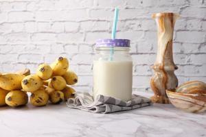 glas melk en bananen op tafel foto