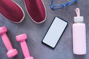 slimme telefoon met sportuitrusting op grijze achtergrond foto