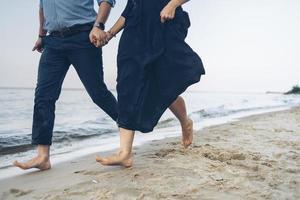 paar loopt langs een strand foto