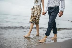 paar blootsvoets lopen op een strand foto