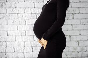 zwangere vrouw in zwarte jurk foto