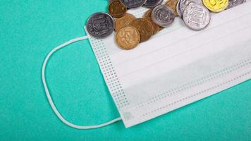stijgende prijzen voor medische maskers, beschermend masker en een handvol munten op een blauwe achtergrond foto