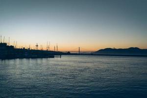 stadssilhouet bij zonsondergang op het water foto
